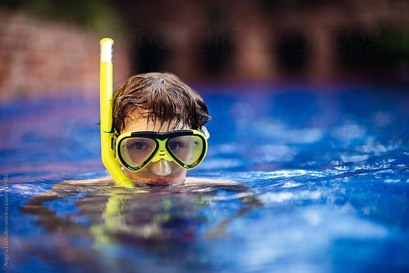 Boy wearing a snorkel set in a pool by Angela Lumsden for Stocksy United