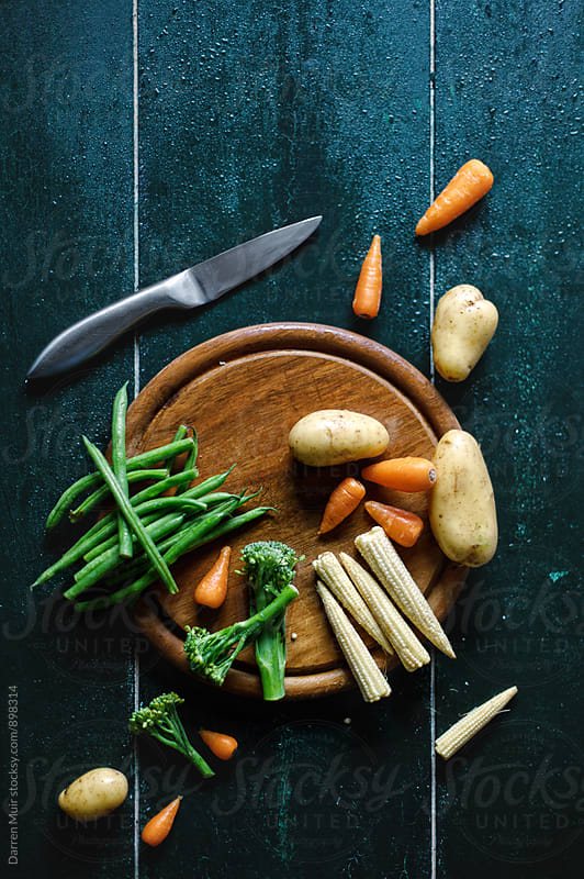 Various fresh vegetable on a wooden cutting board. by Darren Muir for Stocksy United