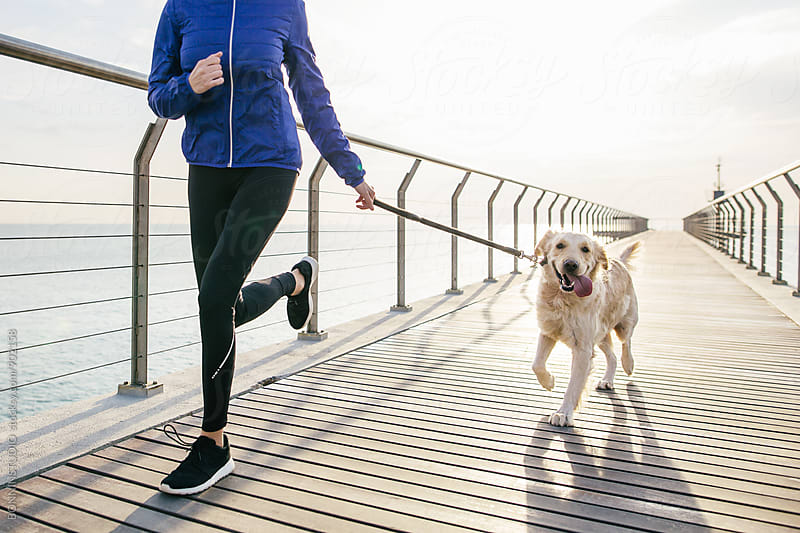 Woman running with her dog on a bridge. by BONNINSTUDIO for Stocksy United