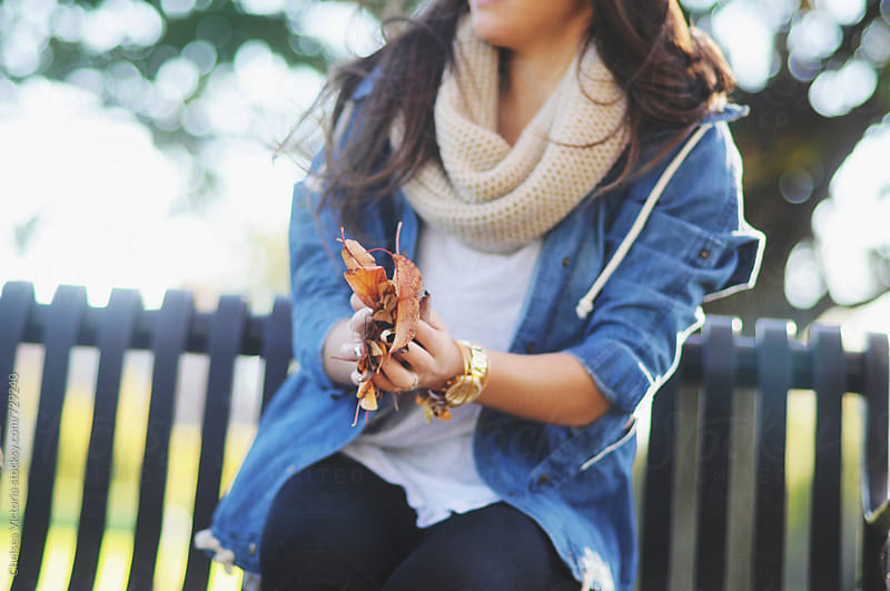 A young woman holding leaves in autumn by Chelsea Victoria for Stocksy United