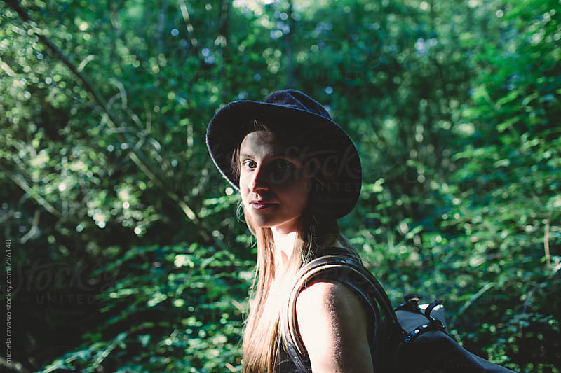Young woman walking in the forest looking at camera by michela ravasio for Stocksy United