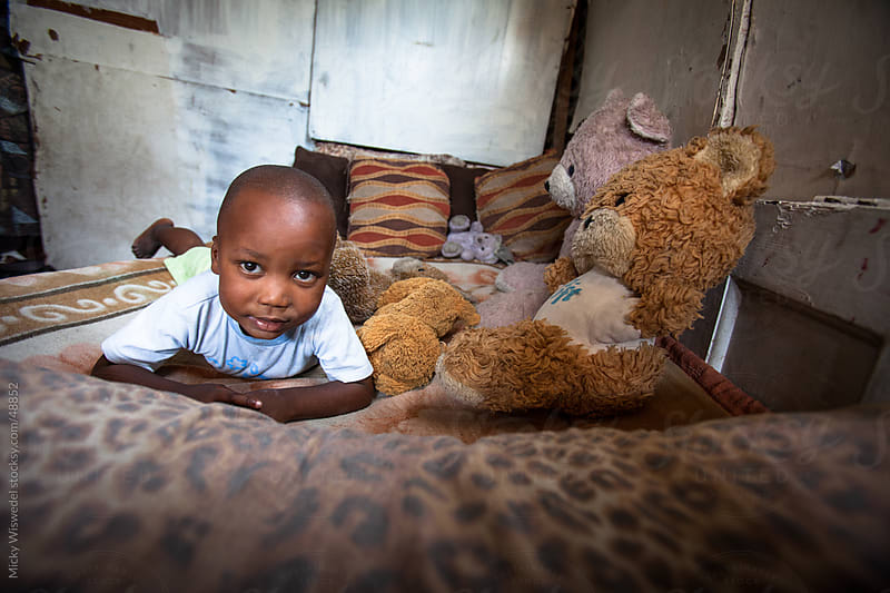 African boy on his bed with a teddy bear by Micky Wiswedel for Stocksy United
