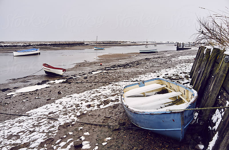 Boats and snow at low tide. Burnham Overy Staithe, Norfolk, UK. by Liam Grant for Stocksy United