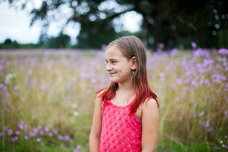 Girl with red tipped hair stands in front of flowery meadow by Carleton Photography for Stocksy United