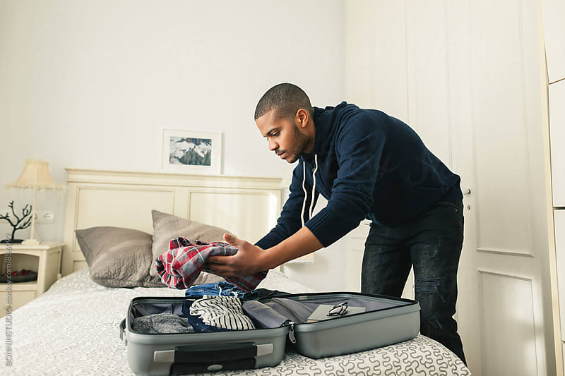 Latin man packs his suitcase for a trip. by BONNINSTUDIO for Stocksy United