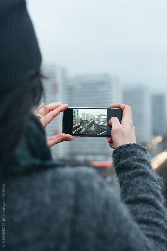 Woman Taking Photo with Smartphone on Berlin Rooftop on Rainy Day by VISUALSPECTRUM for Stocksy United