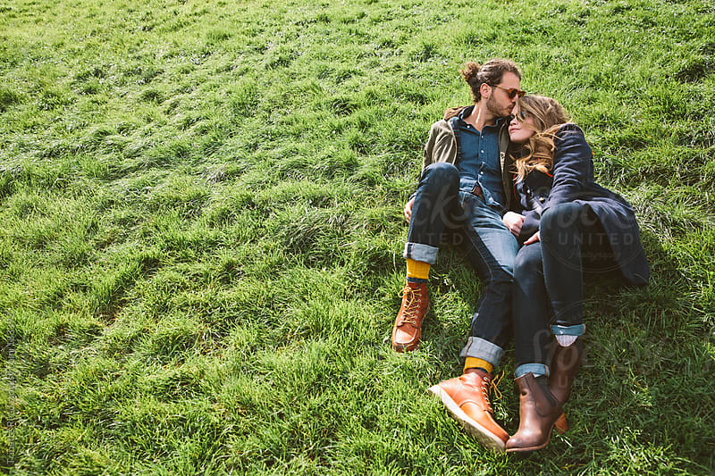Couple relaxing in grass at city park by Trinette Reed for Stocksy United