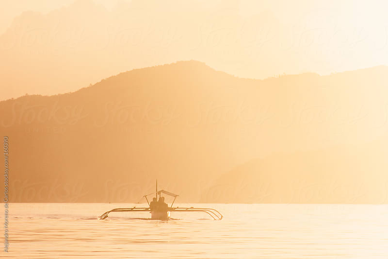 Traditional boat on sea at sunset with mountains in Phillipines by Alejandro Moreno de Carlos for Stocksy United