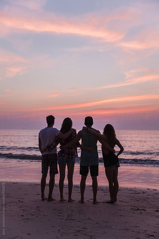 Group of friends watching sunset together at the beach by Jovo Jovanovic for Stocksy United