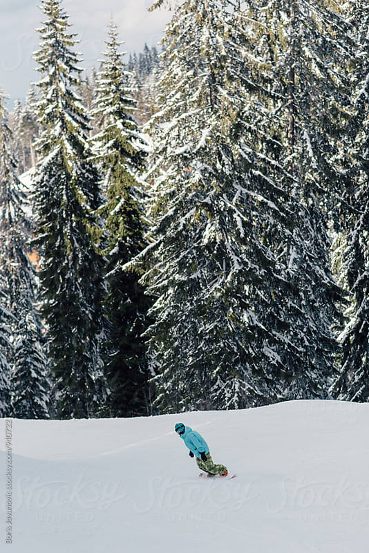 Woman riding a snowboard down the track by Boris Jovanovic for Stocksy United