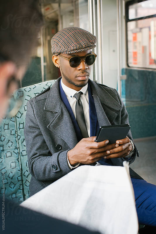 Portrait of Fashionable Black Businessman Reading Ebook in Commuter Train by VISUALSPECTRUM for Stocksy United