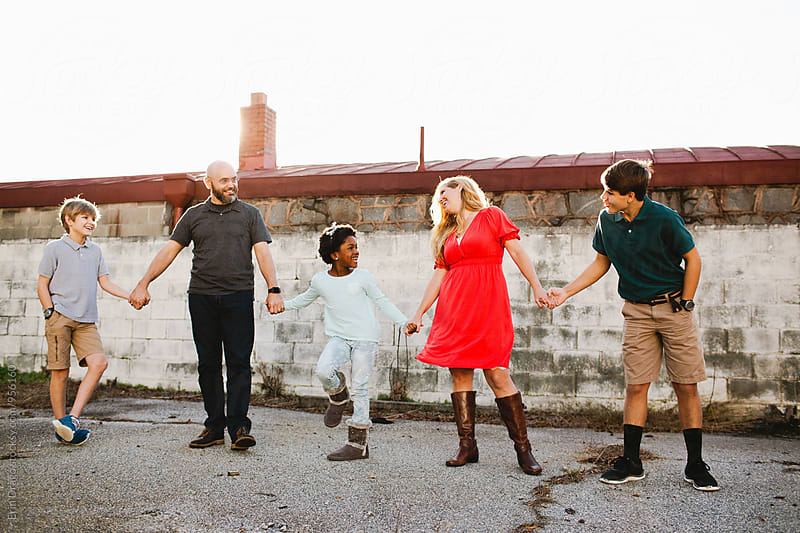 Smiling Multi-Race Family Holding Hands by Erin Drago for Stocksy United