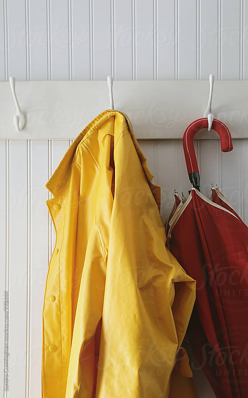 Closeup of rain coat hanging with red umbrella by Sandra Cunningham for Stocksy United