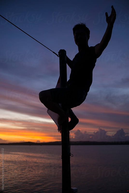 sailor  climb on the mast in sunset by Song Heming for Stocksy United