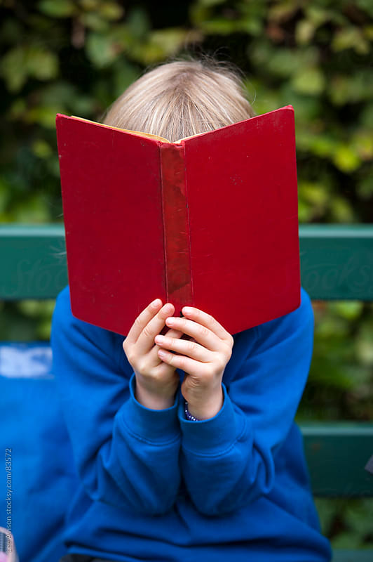 child reading a red book by Lee Avison for Stocksy United