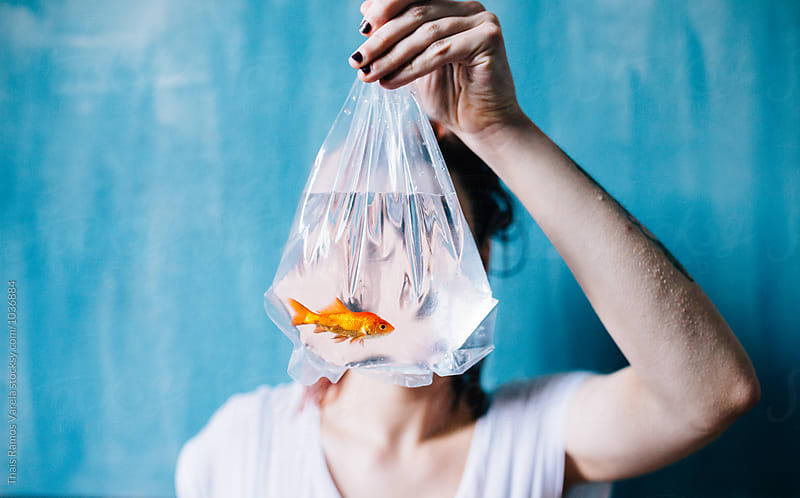 woman with a fish behind her face by Thais Ramos Varela for Stocksy United