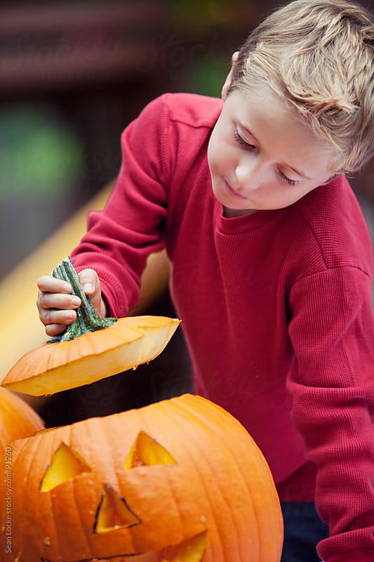 Pumpkins: Young Boy Peeking Into Jack-O-Lantern by Sean Locke for Stocksy United