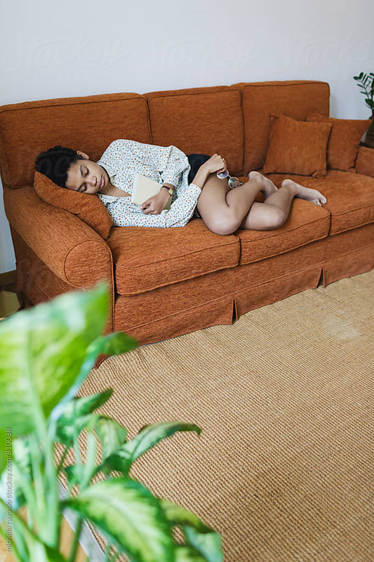 African woman sleeping on the couch at home by michela ravasio for Stocksy United