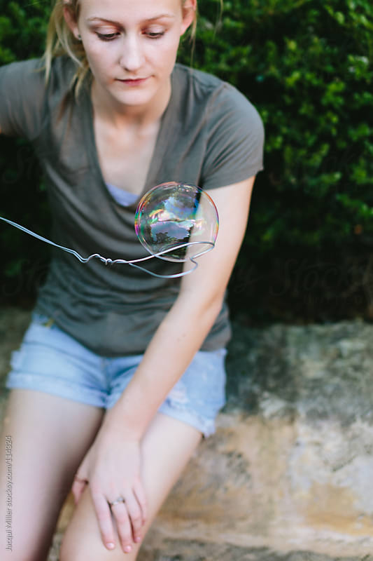 Girl catching a bubble on a handmade heart shaped wire bubble tool by Jacqui Miller for Stocksy United