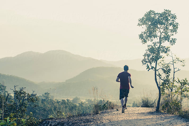 Man running outside in nature at sunset with a mountain background. by Soren Egeberg for Stocksy United