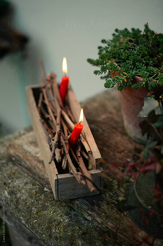 Little red candles burning amongst twigs in wooden box by Laura Stolfi for Stocksy United