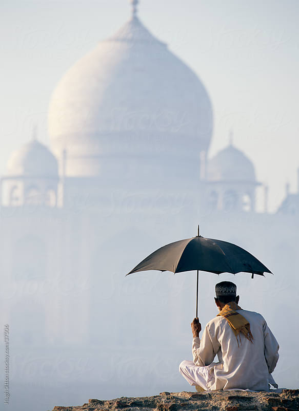 Indian man sitting with umbrella infront of the Taj Mahal.  by Hugh Sitton for Stocksy United