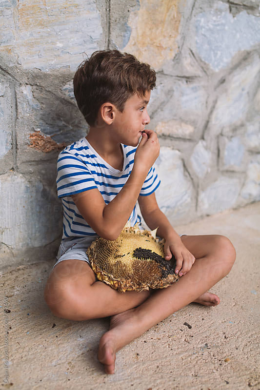 Boy eating sunflower seeds. by Dejan Ristovski for Stocksy United
