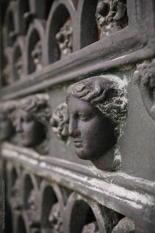 Close-up of decorative woman's head on iron door by Alberto Bogo for Stocksy United