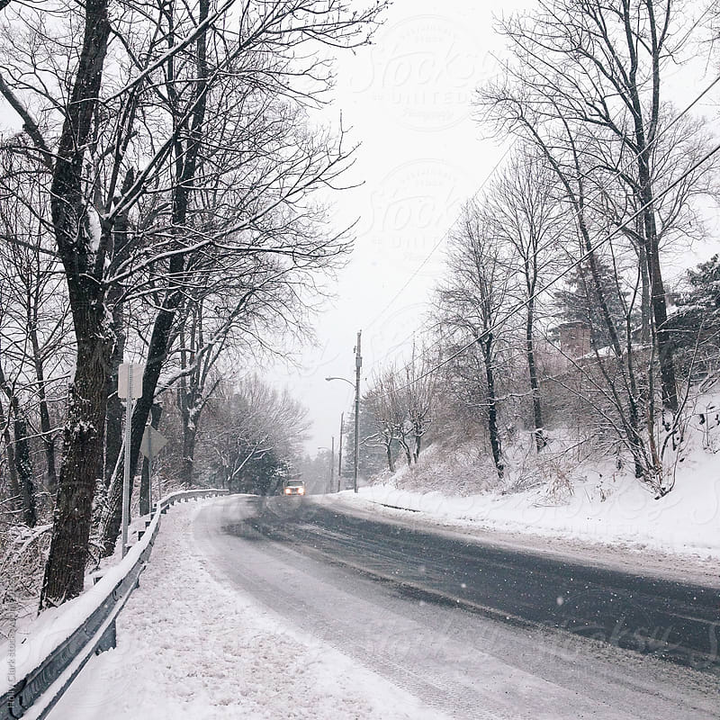 An oncoming car on a snowy road in winter. by Holly Clark for Stocksy United