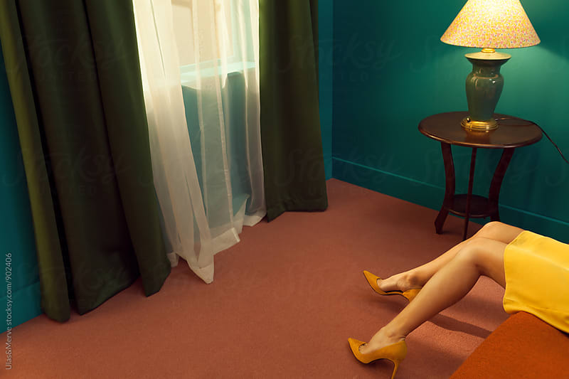 legs of a woman lying down on a bed in a retro room by Ulaş and Merve for Stocksy United