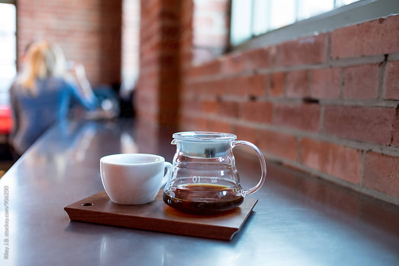 Coffee pot & mug sit on a wooden board at a cafe. by Riley J.B. for Stocksy United