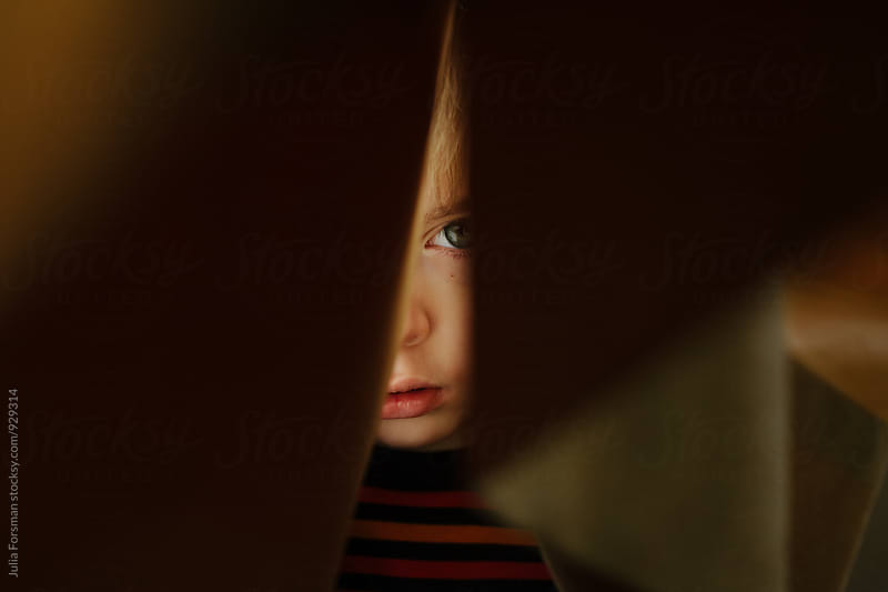Close up of a young boy hiding behind a curtain. by Julia Forsman for Stocksy United