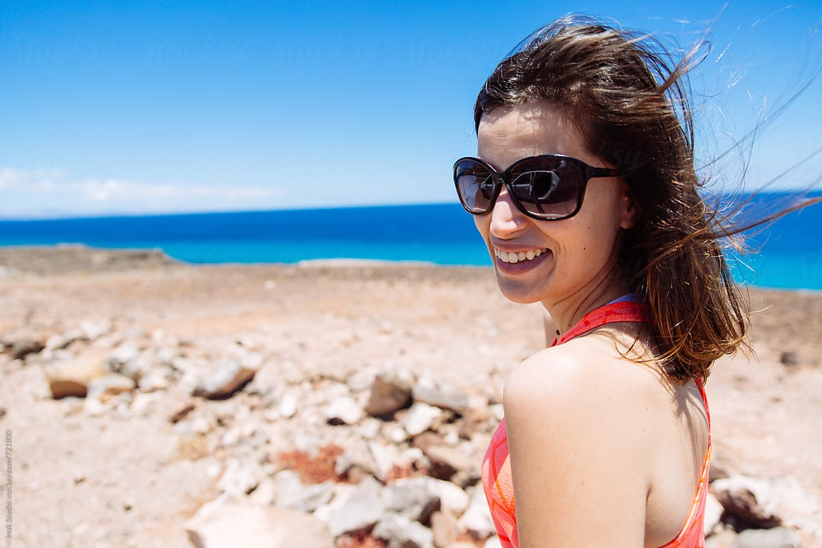 3d7a8bc7cf Young woman portrait wearing sunglasses in a deserted beach on a windy day