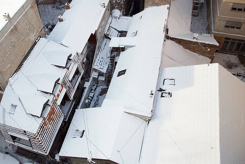 rooftops covered with snow from above by Sonja Lekovic for Stocksy United