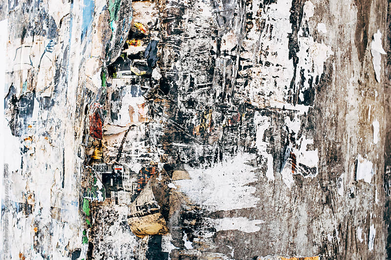Close up peeling and decaying posters on building wall by Paul Edmondson for Stocksy United