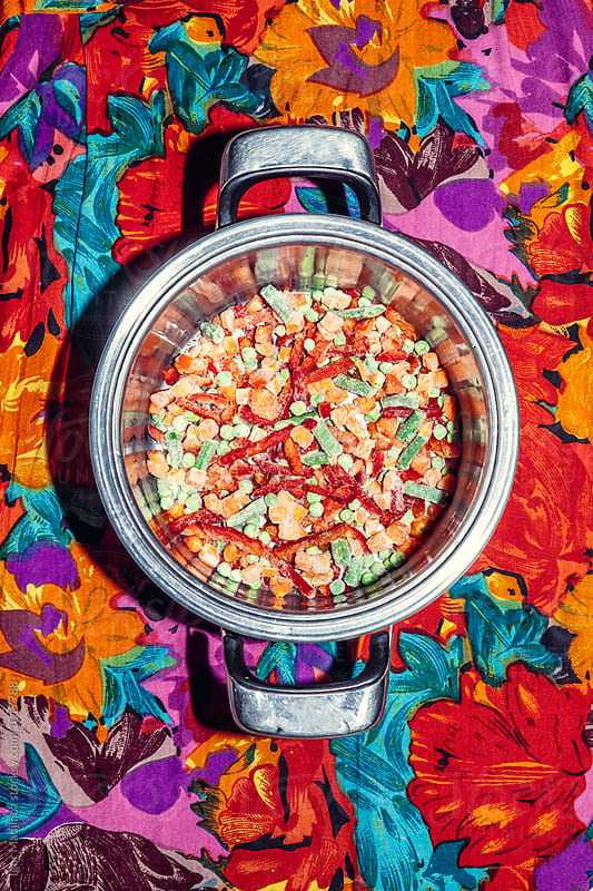 colorful frozen vegetables in metal pot on a table with a colorful tablecloth by Igor Madjinca for Stocksy United