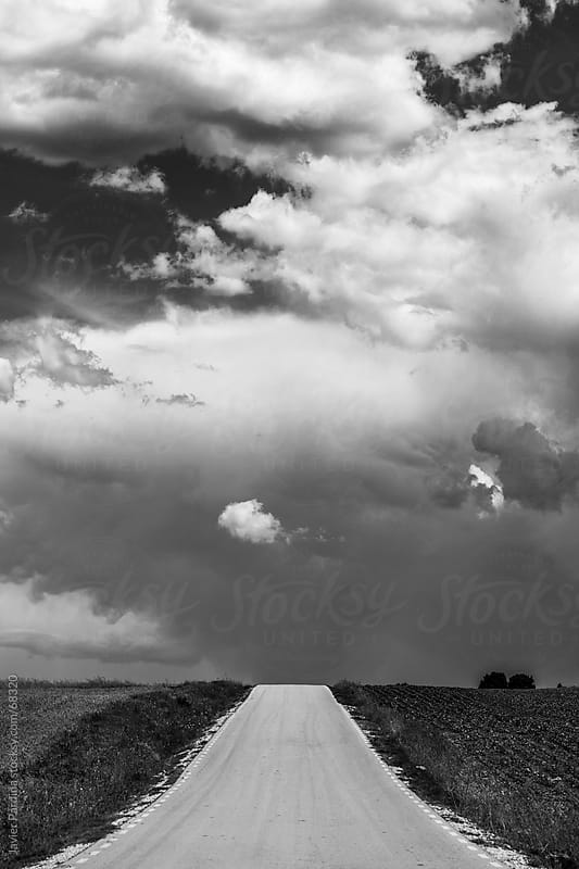 a lonely road to a cloudy sky by Javier Pardina for Stocksy United
