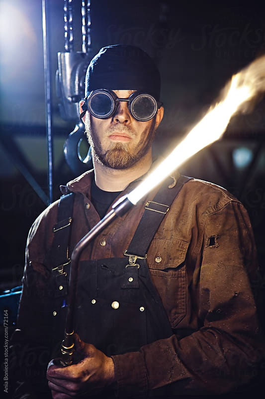 Working class man: Welder with his torch  by Ania Boniecka for Stocksy United