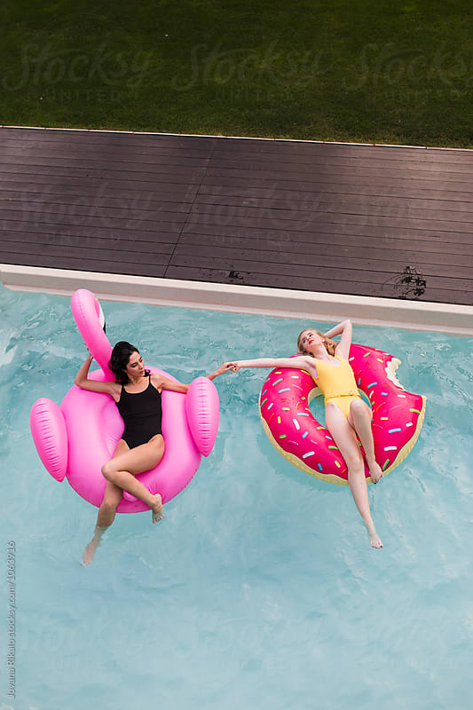 Two female friends floating on a big flamingo in the swimming pool by Jovana Rikalo for Stocksy United