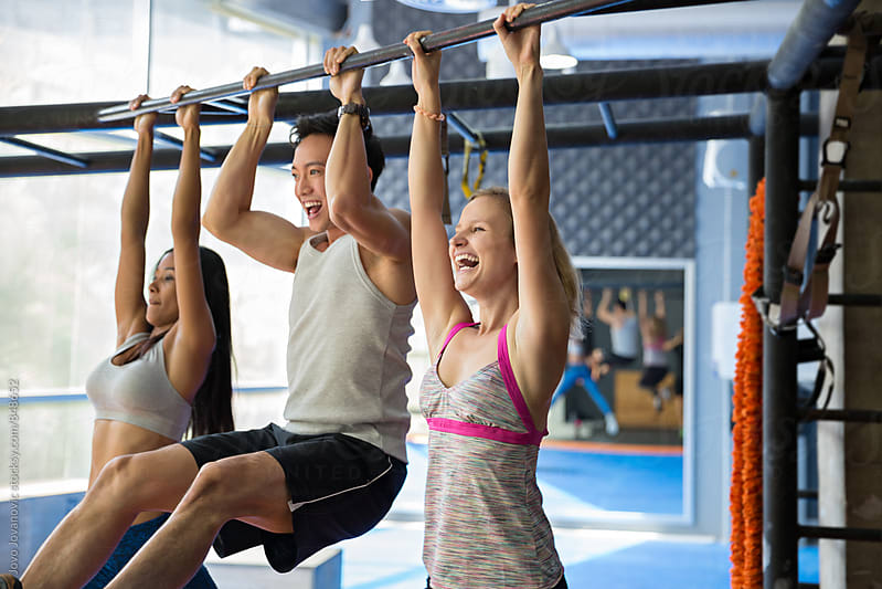 Three workout friends having fun doing pull-ups by Jovo Jovanovic for Stocksy United