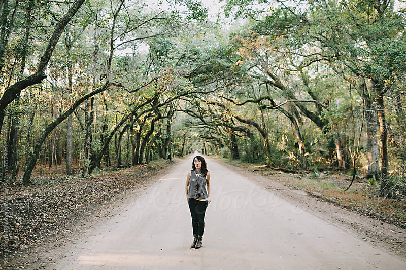 Standing on a tree lined road by Sara K Byrne Photography for Stocksy United