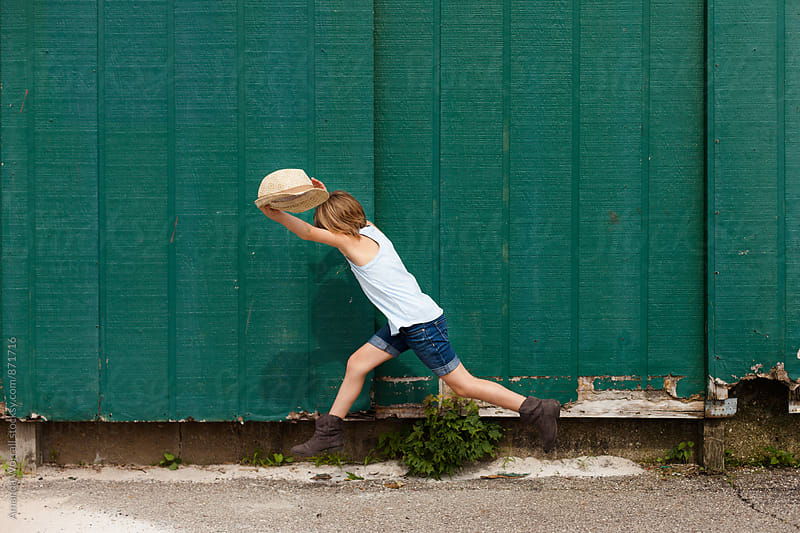 Stylish girl leaping in front of green wall in summer by Amanda Worrall for Stocksy United