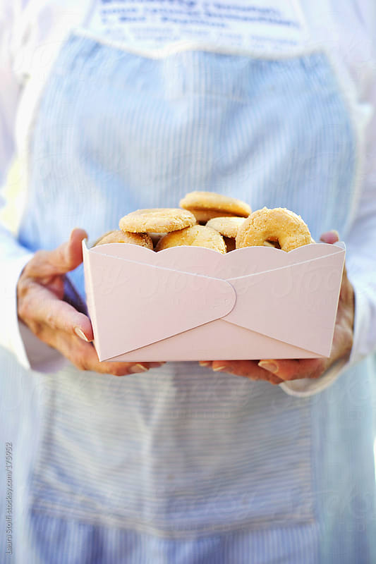 Woman with a pin box full of ring-shaped typical italian biscuit by Laura Stolfi for Stocksy United