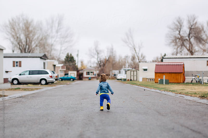 Toddler walking in trailer park by Jessica Byrum for Stocksy United