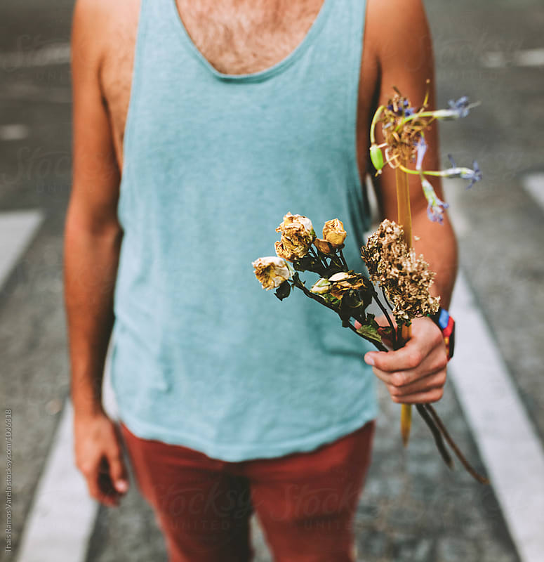 man holding a dry flower bouquet by Thais Ramos Varela for Stocksy United