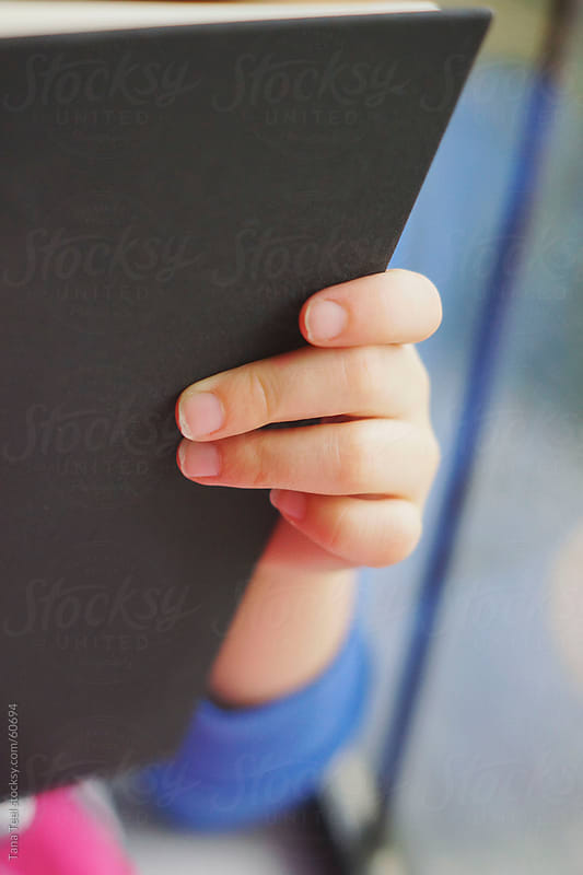 A young girl's fingers grip the edge of the book she's reading by Tana Teel for Stocksy United