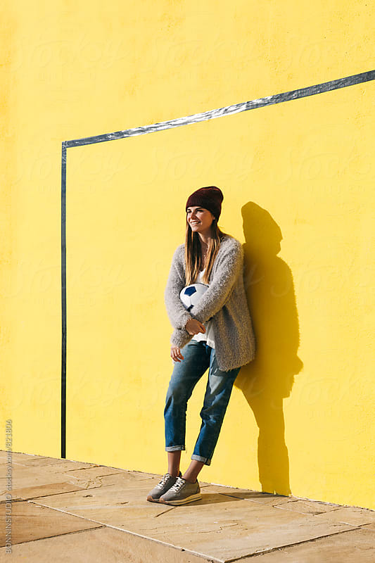 Young woman holding soccer ball in front of a yellow wall. by BONNINSTUDIO for Stocksy United
