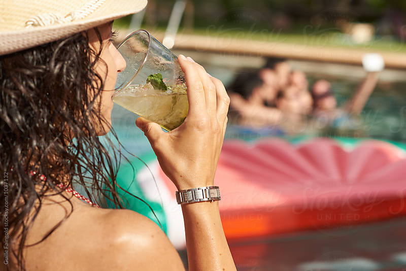 Close-up of brunette drinking mojito against of friends in pool taking selfie by Guille Faingold for Stocksy United