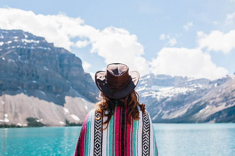 A woman looking out towards the blue waters of a lake by Kristen Curette Hines for Stocksy United