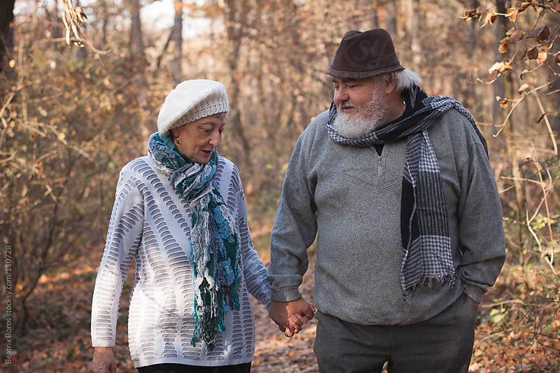Senior couple walking in the forest hand in hand in Autumn by Beatrix Boros for Stocksy United
